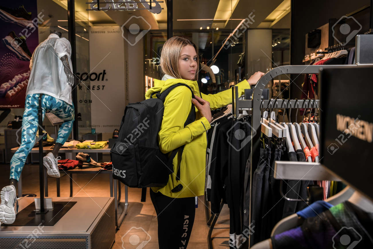 Skopje, North Macedonia - March 12, 2021: Asics store in Skopje, North Macedonia. Girl photo model wearing sports tracksuits and sneakers ASICS GEL, carrying a sports backpack on her shoulder - 166164680