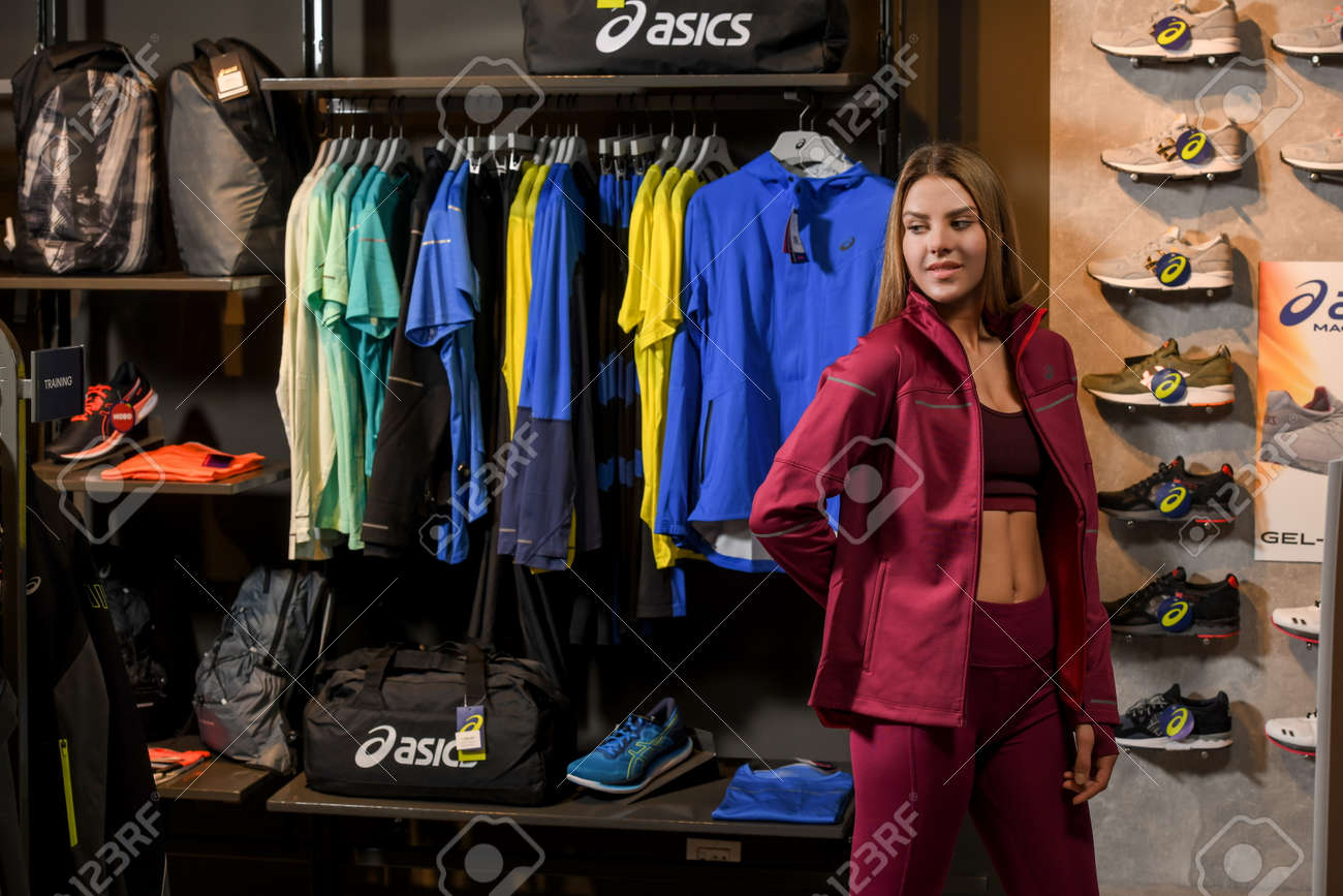 Skopje, Northern Macedonia - March 12, 2021: Asix store in Skopje, Northern Macedonia. Girl photo model wearing a set of dark red tracksuits and sneakers ASICS GEL, standing posing in a sports shop - 166164708