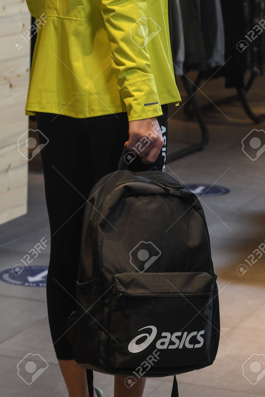 Skopje, North Macedonia - March 12, 2021: Asics store in Skopje, North Macedonia. Girl model wearing sports tracksuits and sneakers ASICS GEL, holding a sports backpack - 166241062