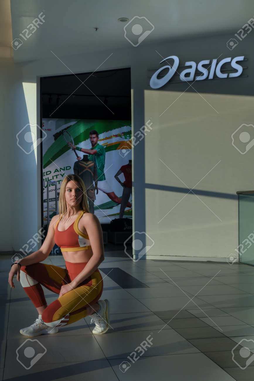 Skopje, Northern Macedonia - March 12, 2021: Asics store in Skopje, Northern Macedonia. Girl photo model wearing sports tracksuits and sneakers ASICS GEL, kneeling posing in front of a sports shop - 166164681