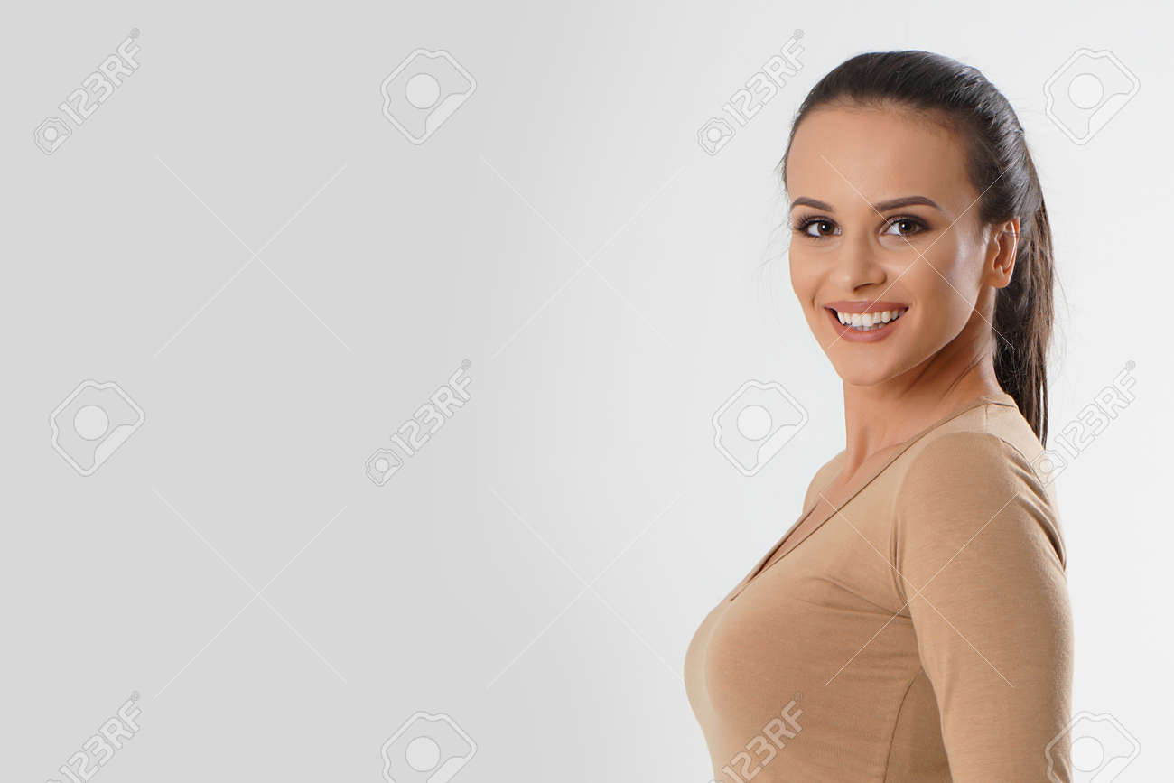 Portrait of young beautiful cute cheerful girl smiling looking at camera over white background. Woman portrait natural beautiful. Young attractive smiling woman in brown blouse looking at camera - 166482598
