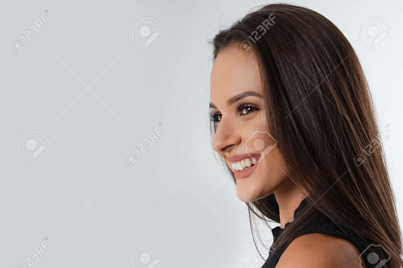 Portrait of an emotionally beautiful woman laughing while looking to the side. Beauty face portrait. Beautiful model girl with perfect fresh clean skin. Concept for youth and skin care - 166560983