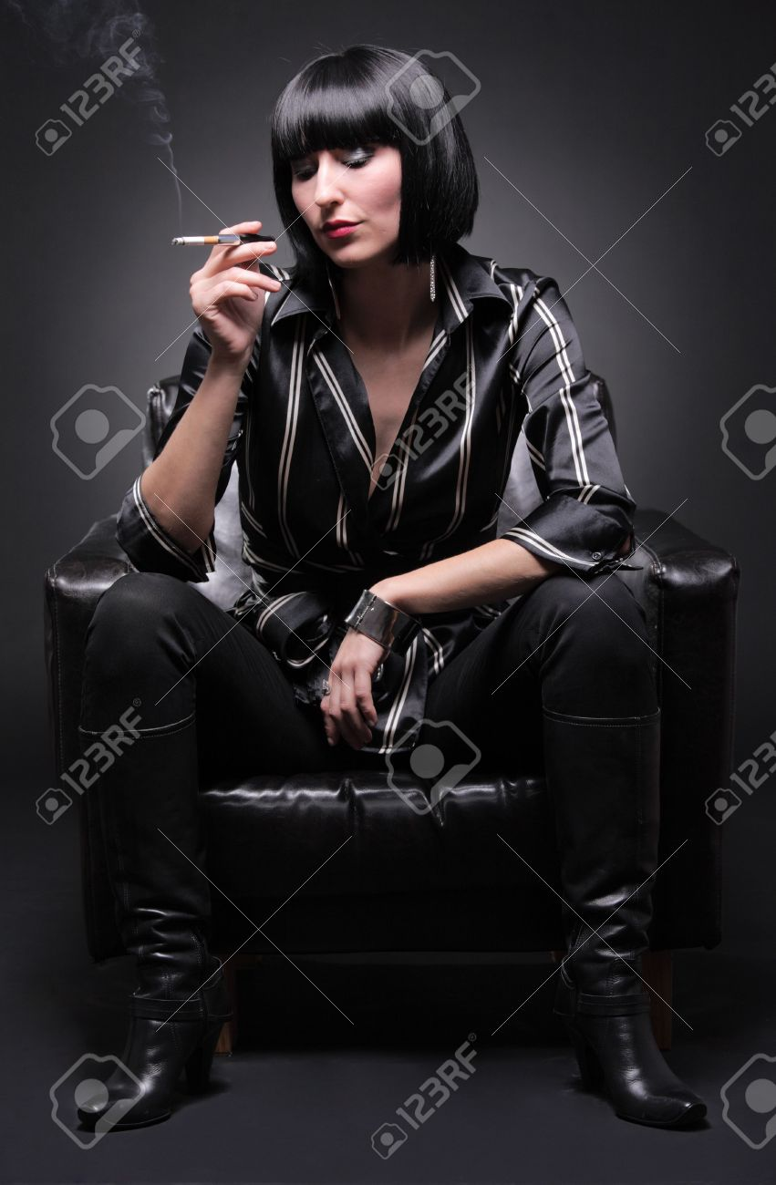Fashionable young woman sitting in an armchair having a cigarette Stock Photo - 3966008