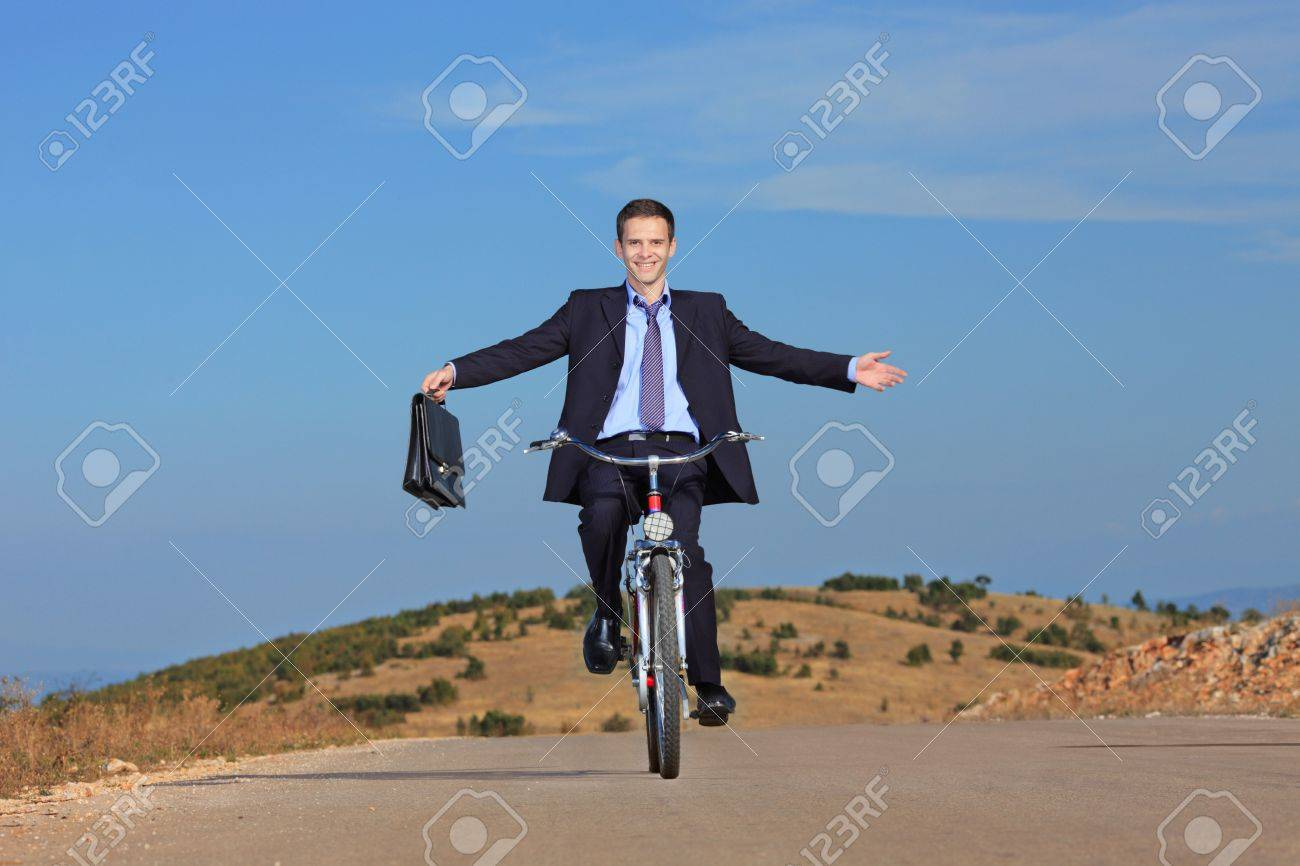 Carefree businessman holding a briefcase and riding a bicycle outdoors - 5652124