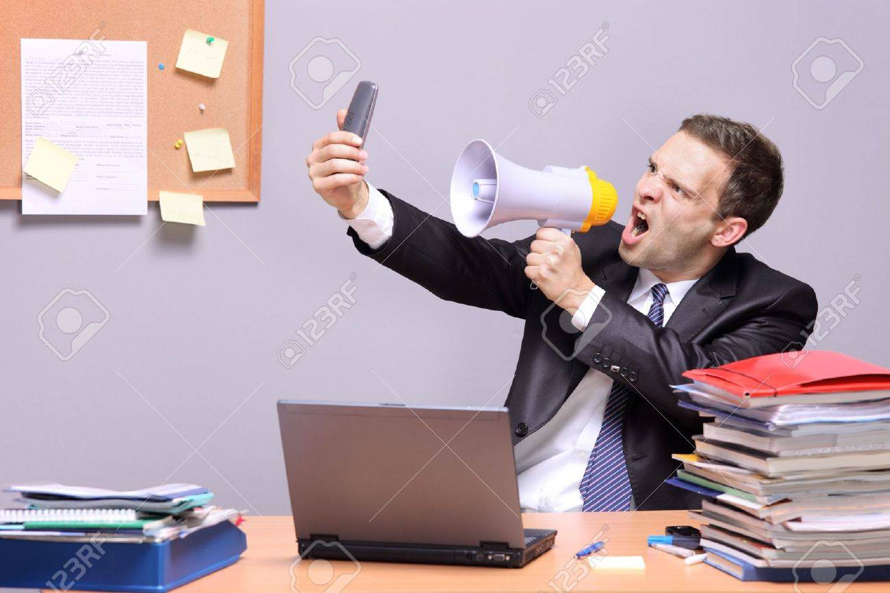 Frustrated office worker on the phone holding stock photo image - Frustrated Phone Angry Businessman In An Office Shouting On A Megaphone Holding A