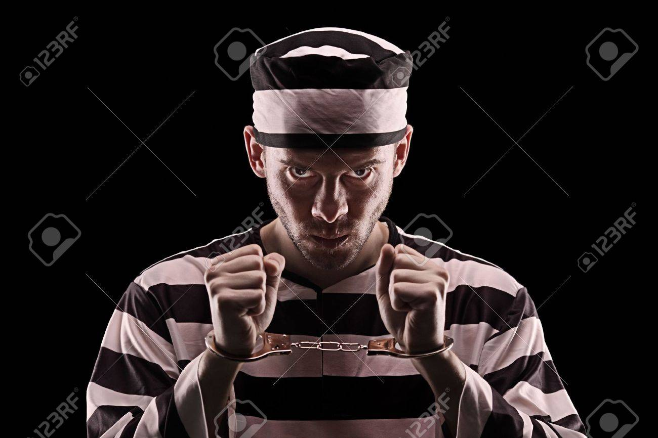 Angry prisoner with handcuffs isolated on black background Stock Photo - 6530334