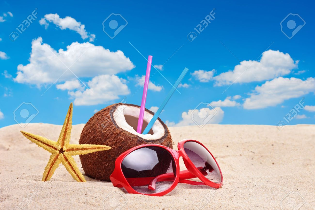A coconut, starfish and a sunglasses on a beach Stock Photo - 7329749