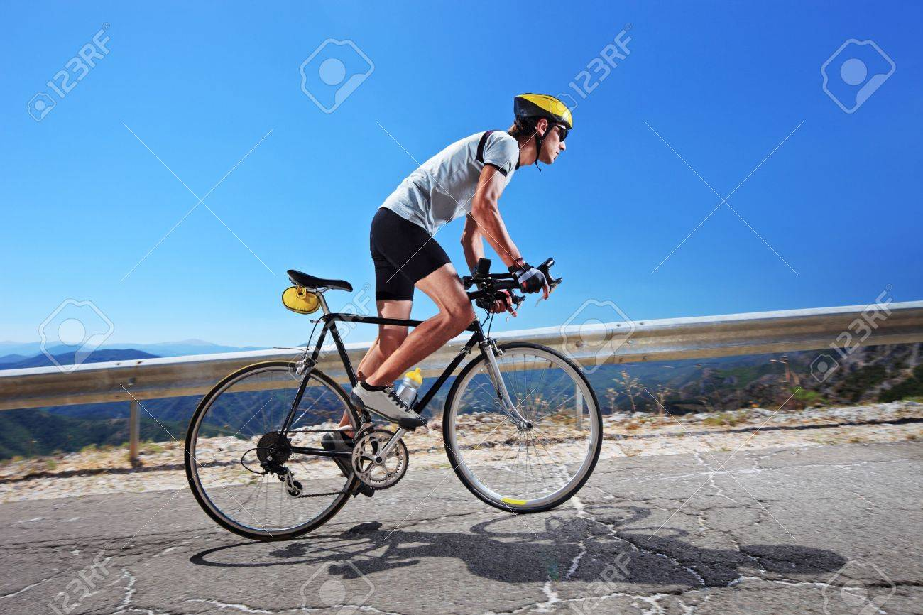 A male cyclist riding a bike uphill along a road; clear summer day Stock Photo - 8038052