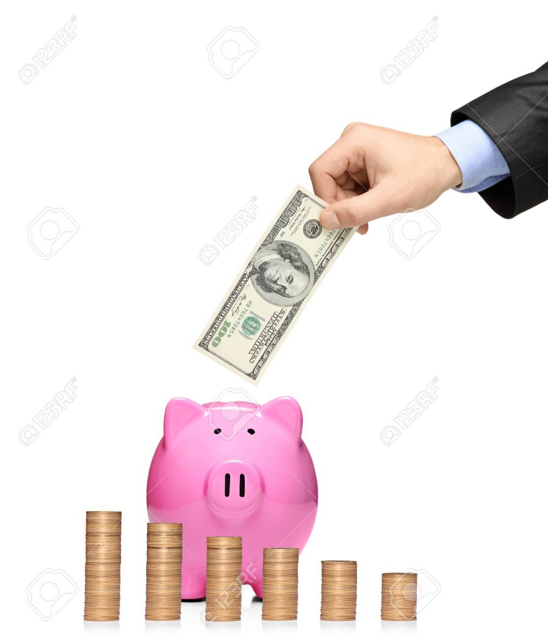 Man inserting a dollar into a piggy bank with stack of coins in front showing growth isolated against white background Stock Photo - 8189576