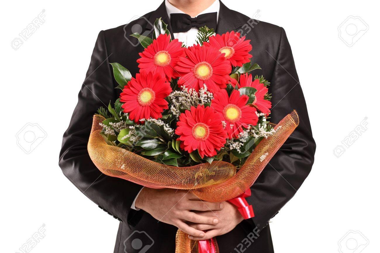 Парень с букетом цветов в руках фото