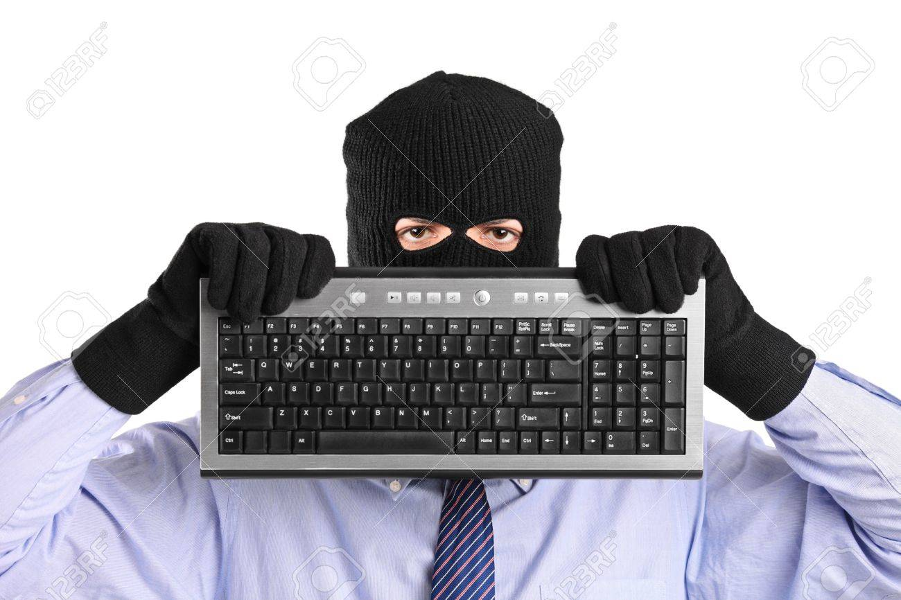 A hacker with robbery mask holding a keyboard isolated on white background Stock Photo - 8711729
