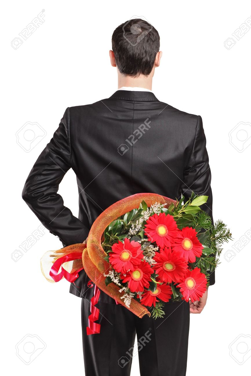 Man Wearing Black Suit Hiding A Bouquet Of Flowers Behind His