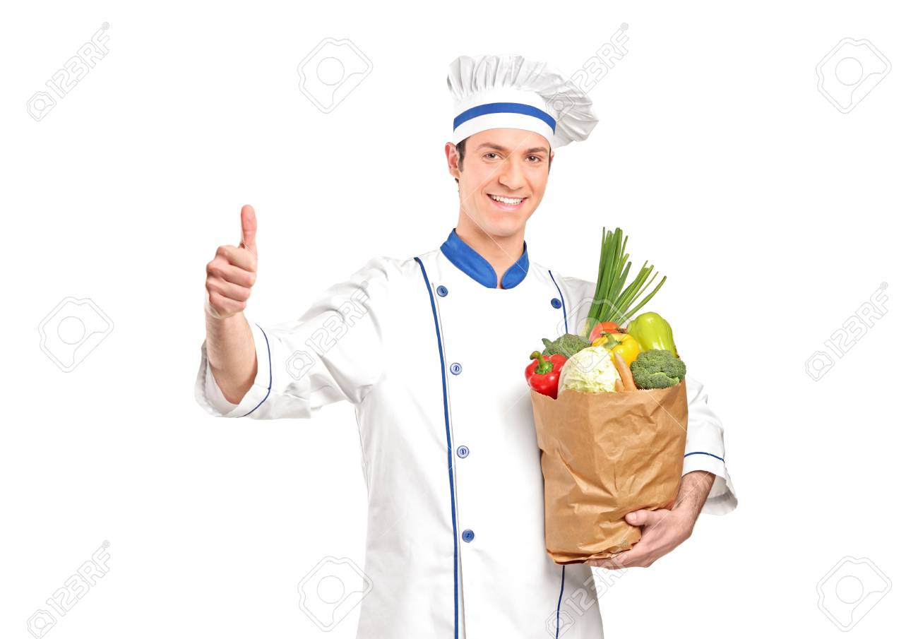 A chef giving thumb up and holding a grocery bag full with vegetables isolated on white background Stock Photo - 9093724