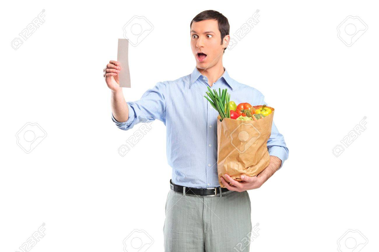 Shocked man looking at store receipt and holding a grocery bag isolated on white background Stock Photo - 9093748