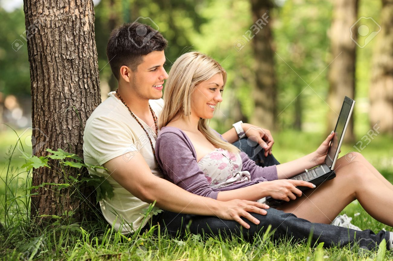 A Boyfriend And Girlfriend Working On A Laptop In A Park Stock Photo,  Picture And Royalty Free Image. Image 9986618.