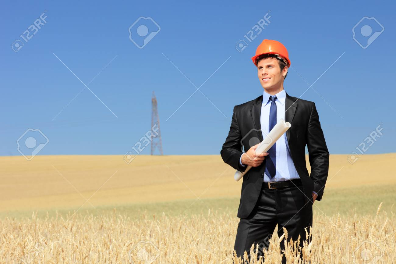 Young architect wearing protective helmet and holding blueprints in a wheat field Stock Photo - 9997260