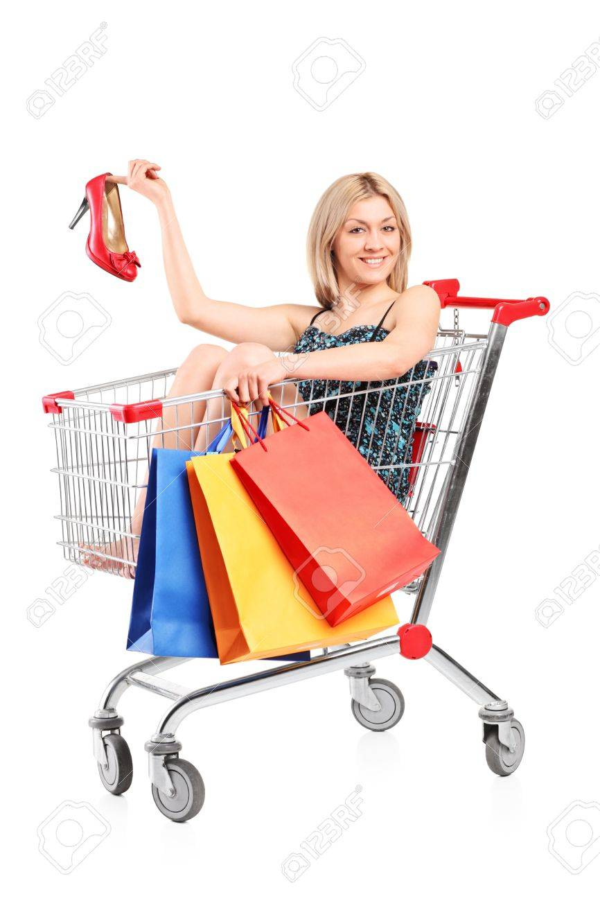 Woman posing with shopping bags isolated on white background full - A Blond Woman With Shopping Bags Posing Into A Shopping Cart Holding A Shoe Isolated On