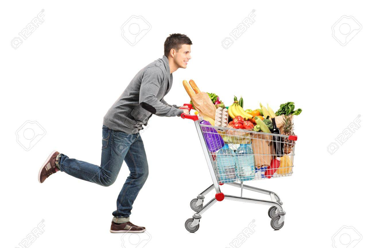 Young man running and pushing a shopping cart full with food isolated on white background Stock Photo - 11744274
