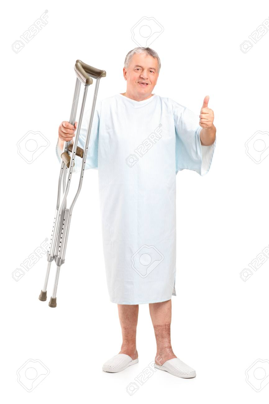 Full length portrait of a senior patient holding crutches and giving thumb up isolated on white background Stock Photo - 11744573