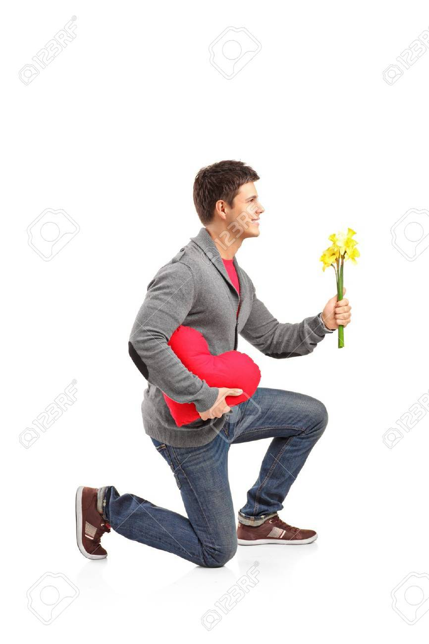 Man Shaped Pillow A Young Man Holding A Heart Shaped Pillow And Bunch Of Flowers