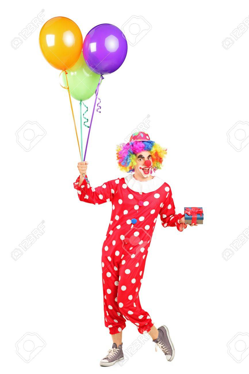 Full length portrait of a male clown, happy joyful expression on face, with a bunch of balloons and a gift isolated on white background Stock Photo - 14286218