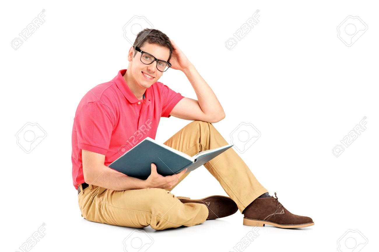young man sitting on floor and reading a book isolated on white