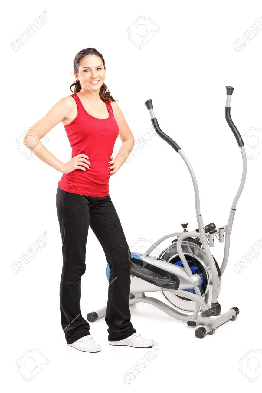 Young female posing next to a cross trainer isolated on white background Stock Photo - 15442844