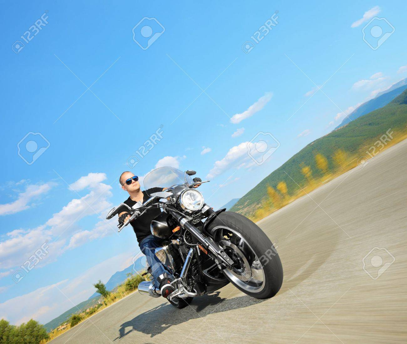 Biker riding a customized motorcycle on an open road Stock Photo - 15636591