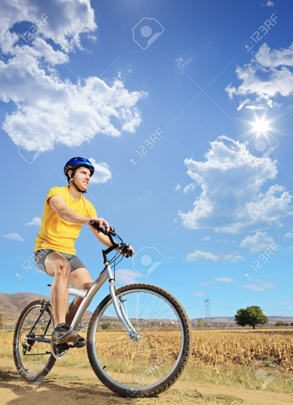 A young male in yellow shirt riding a bike on a sunny day in Macedonia Stock Photo - 16064942