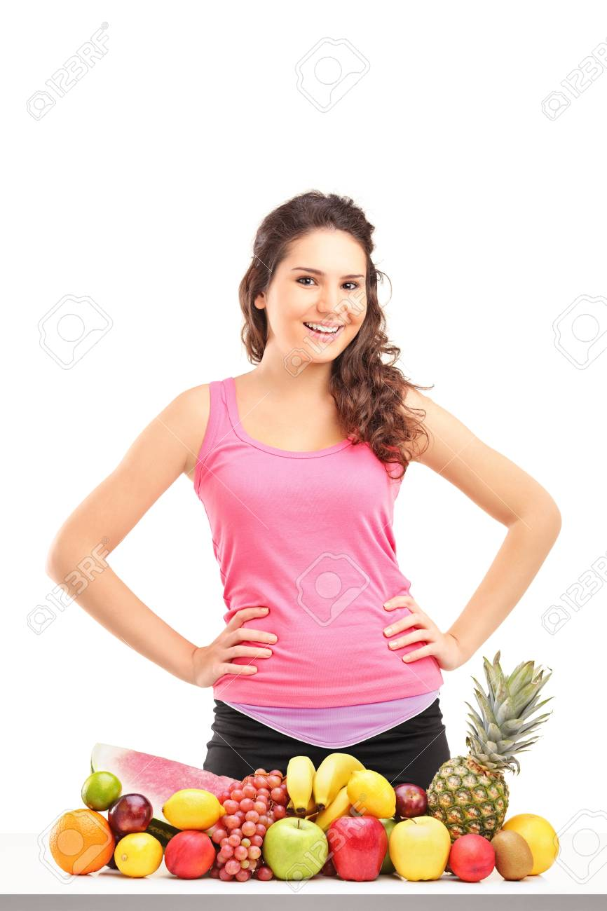 Young female athlete posing behind a pile of different fruits isolated on white background Stock Photo - 16547499