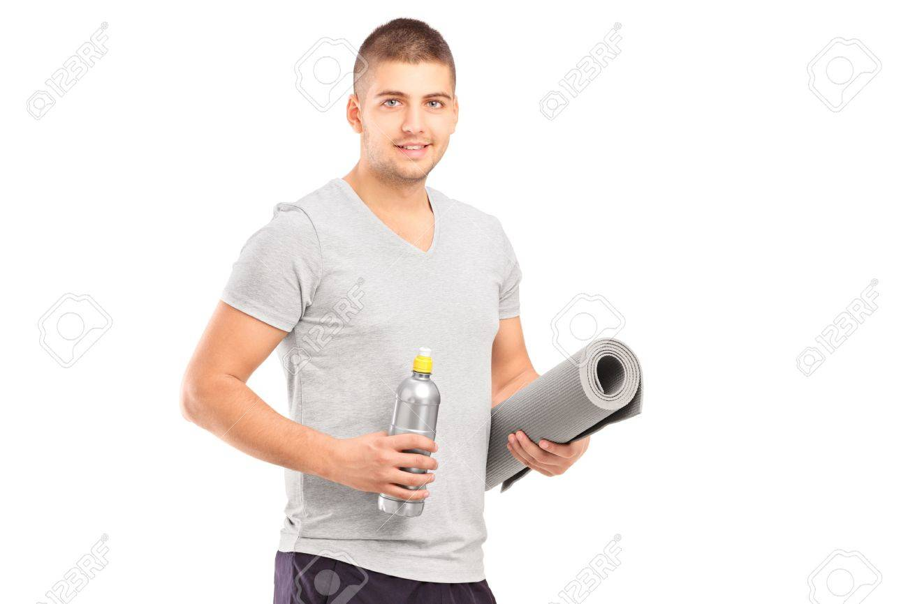 A male holding a bottle of refreshment drink and a mat after an excerise isolated on white Stock Photo - 16639733
