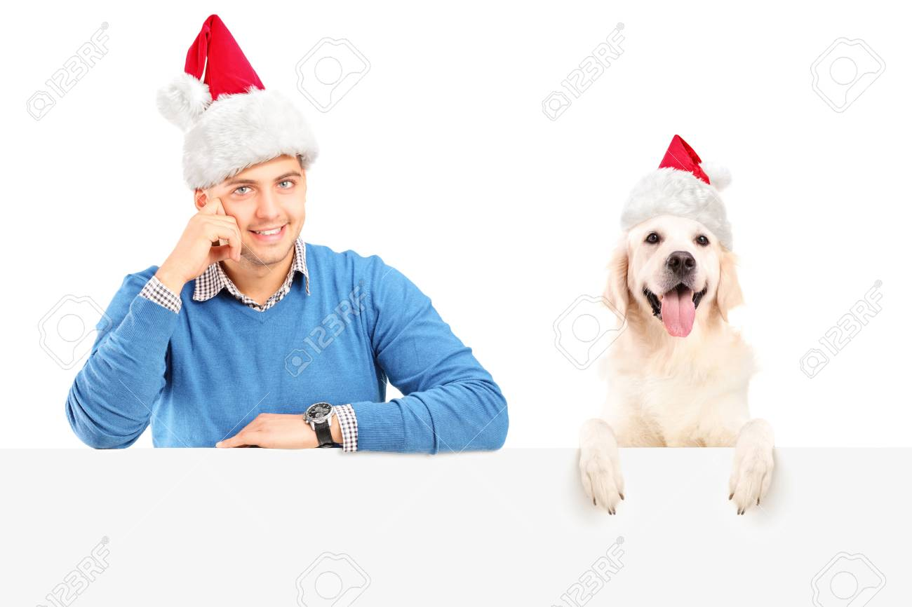 Smiling guy and dog wearing santa claus hats and posing behind a blank panel Stock Photo - 16639712
