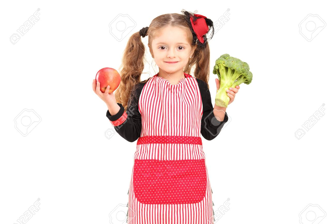 e9b19f9a0fa4 A smiling girl with apron holding a broccoli and red apple isolated against white  background Stock