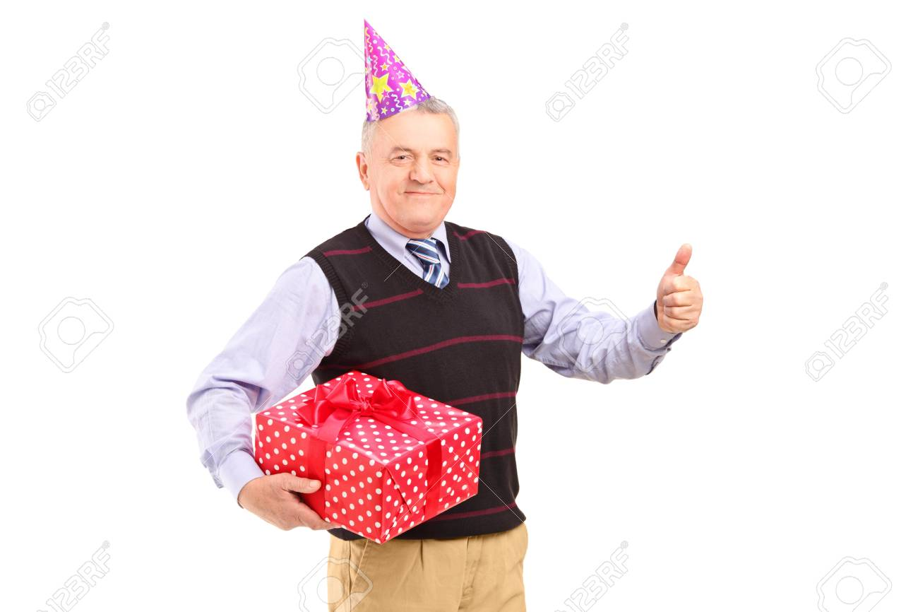 A gentleman with party hat holding a gift and giving a thumb up isolated on white background Stock Photo - 17098861