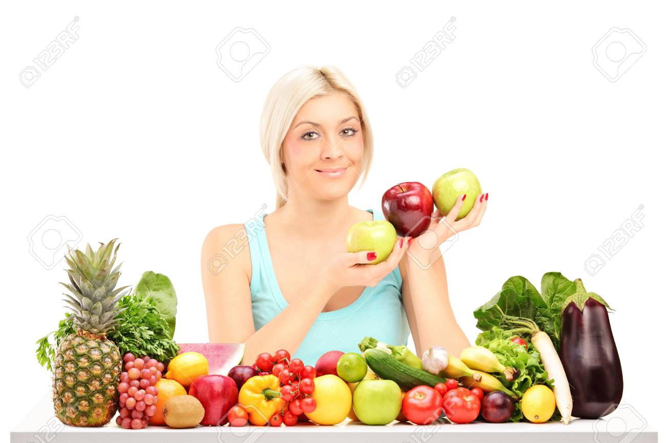 Beautiful young woman holding apples behind a table full of fruits and vegetables isolated on white background Stock Photo - 17052558
