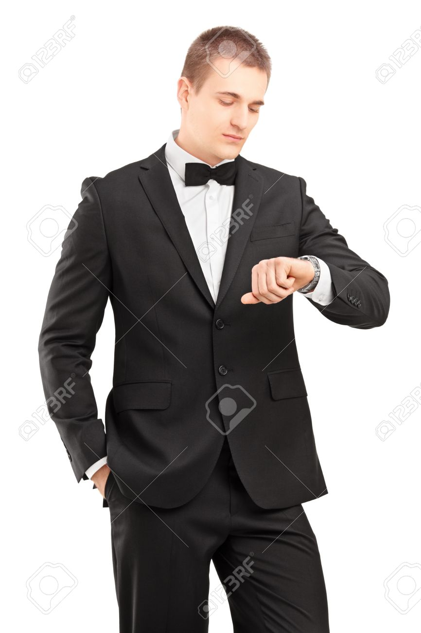 4bcfb9bf8c827 A young man in black suit with bow tie looking at wrist watch isolated on  white