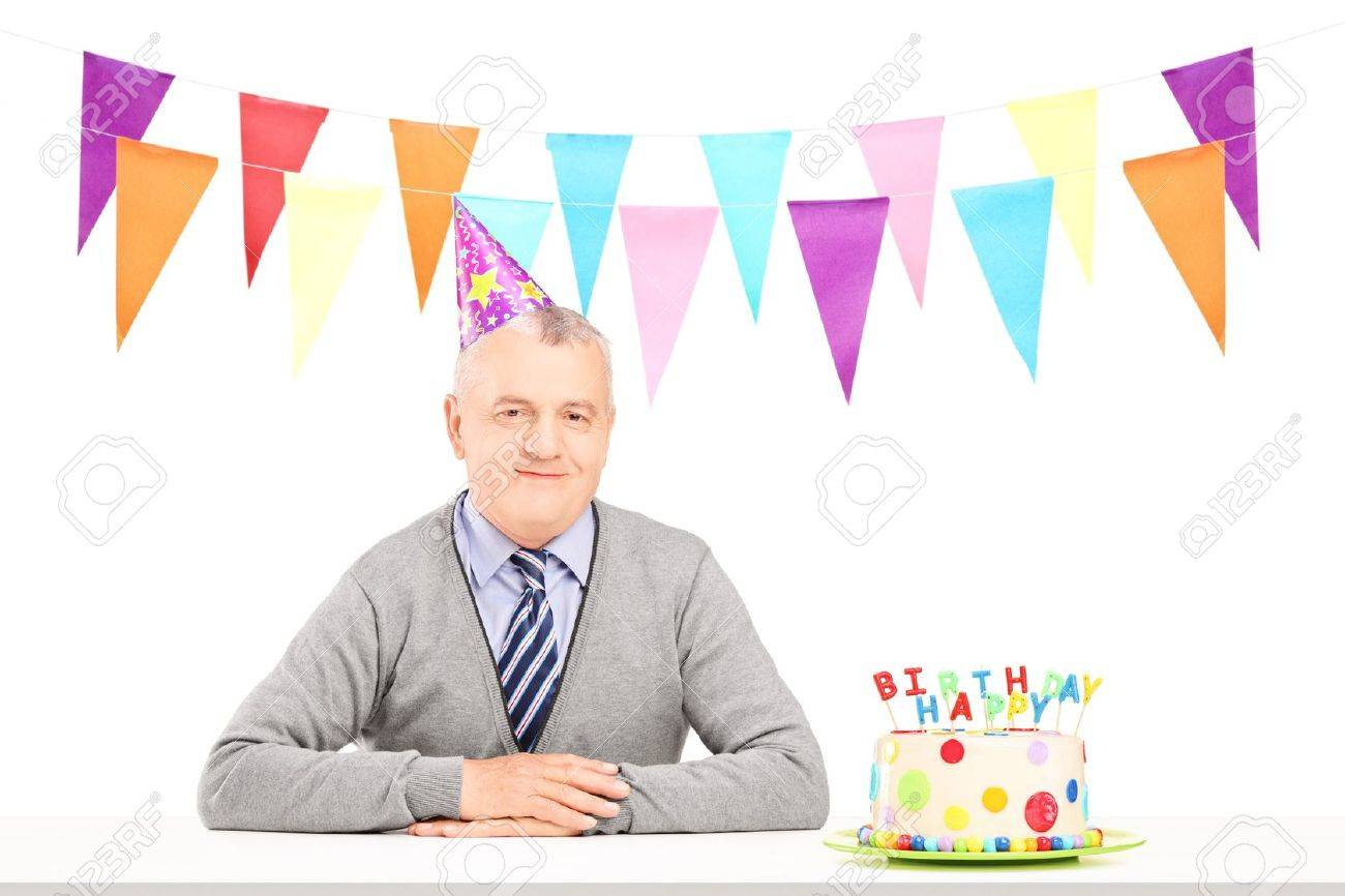 Happy Mature Gentleman With Party Hat And A Birthday Cake Isolated