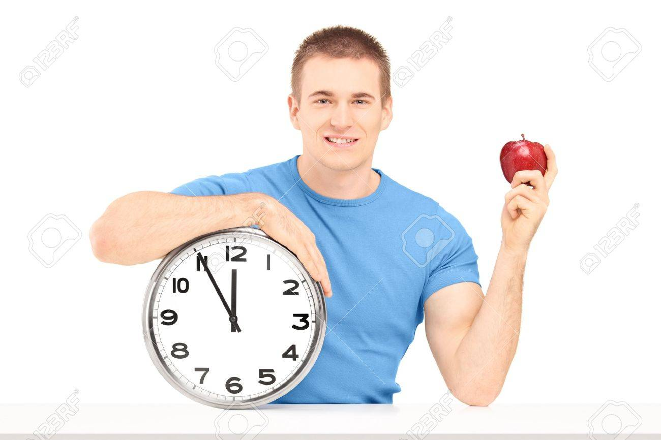 A smiling guy holding a wall clock and red apple on a table isolated on white background Stock Photo - 19362220