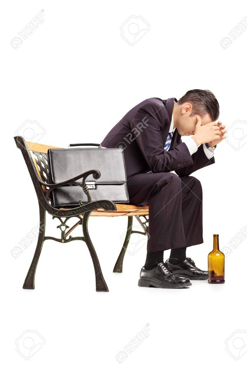 Disappointed young businessperson sitting on a wooden bench isolated on white background Stock Photo - 21381846