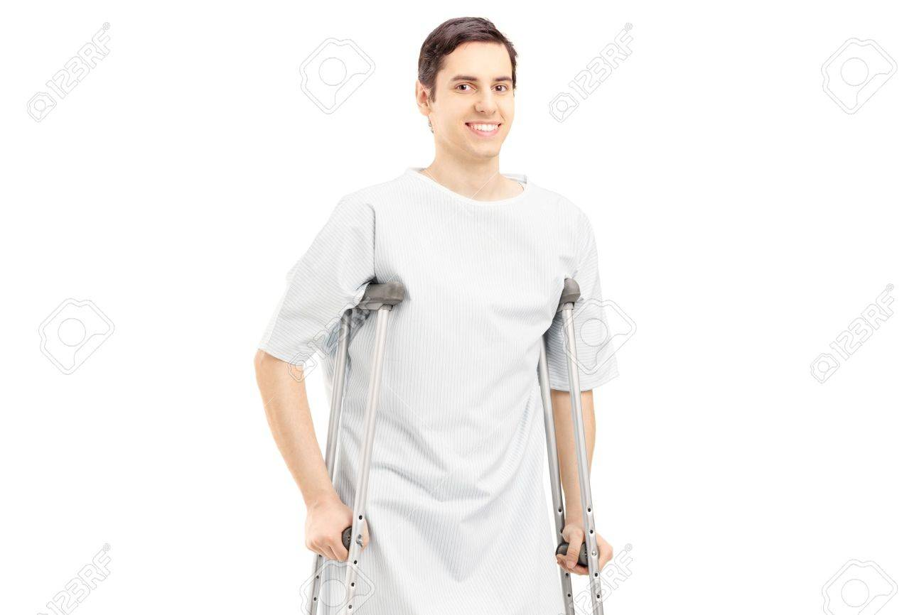 Smiling Male Patient In Hospital Gown With Crutches Isolated.. Stock ...