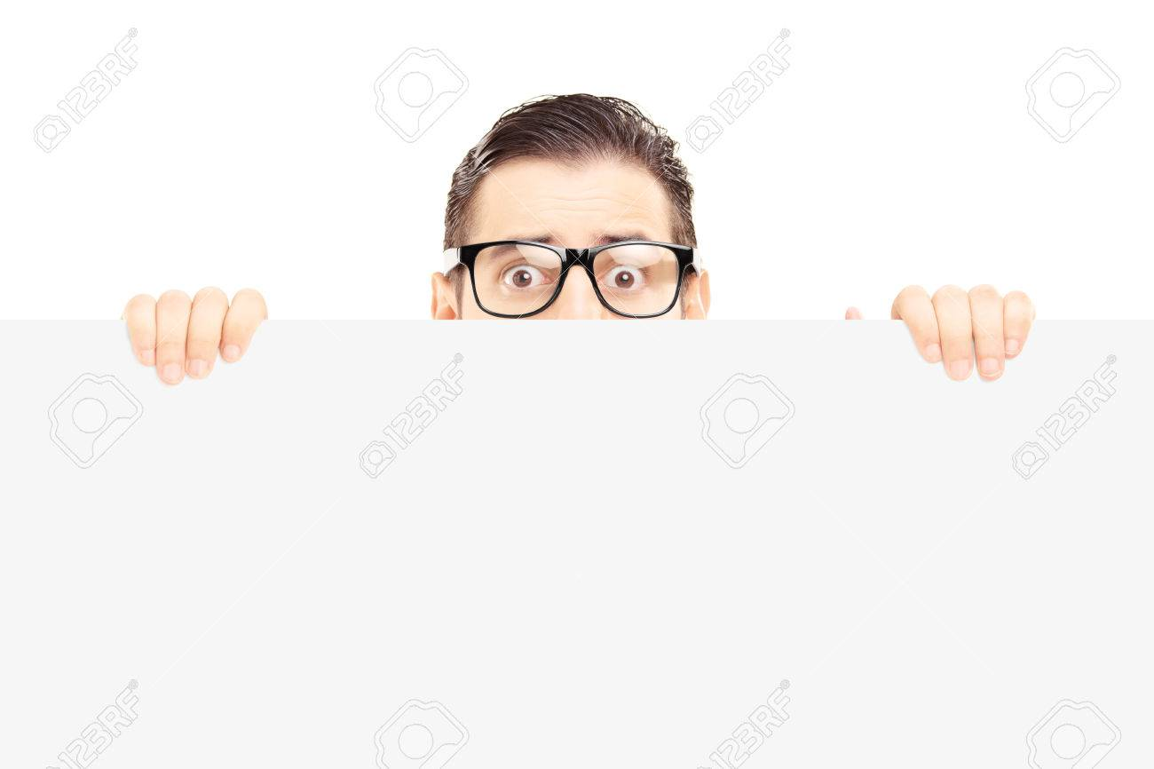 Scared young man with glasses hiding behind a blank panel isolated on white background Stock Photo - 22309868