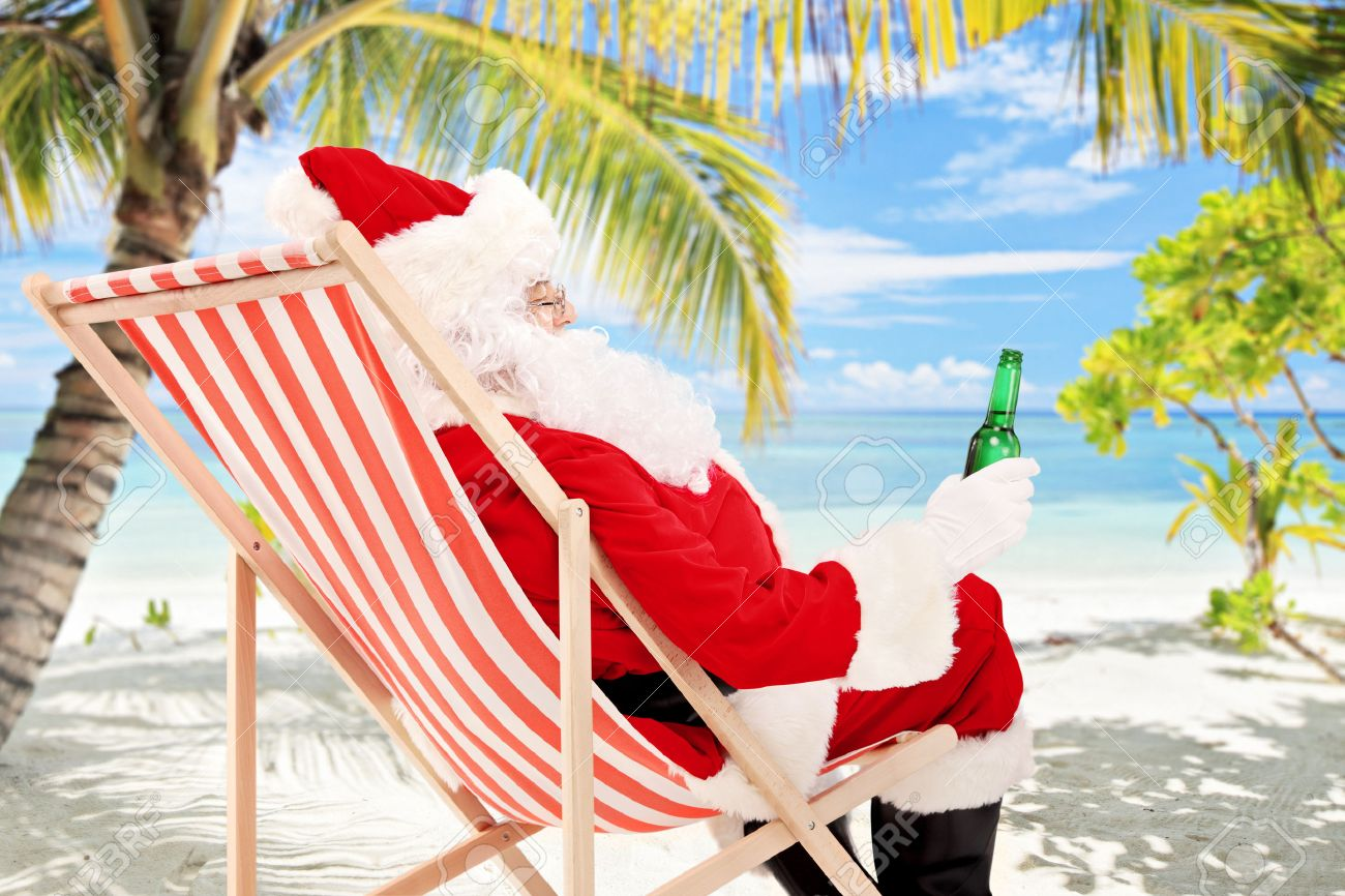 Santa Claus on a beach chair drinking beer and enjoying on a sunny day, on a tropical beach - 22553779