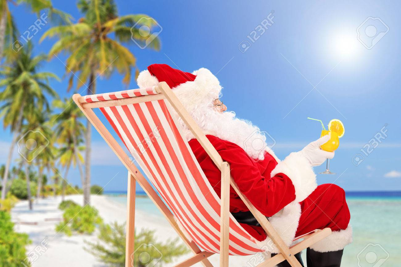 Santa Claus lying on a beach chair and drinking orange cocktail, enjoying on a sunny day, on a beach - 22875097