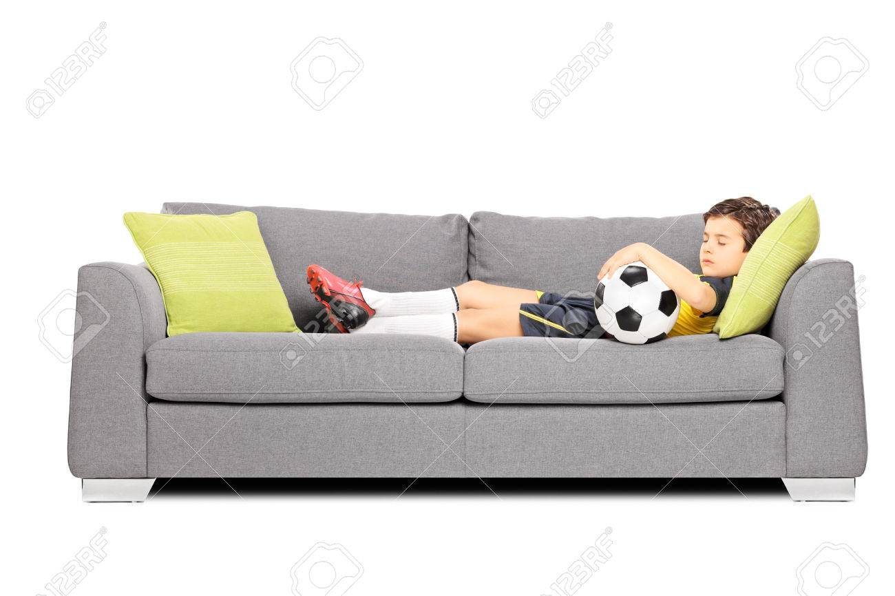 Boy in sportswear with a soccer ball sleeping on a modern sofa isolated on white background Stock Photo - 24460107