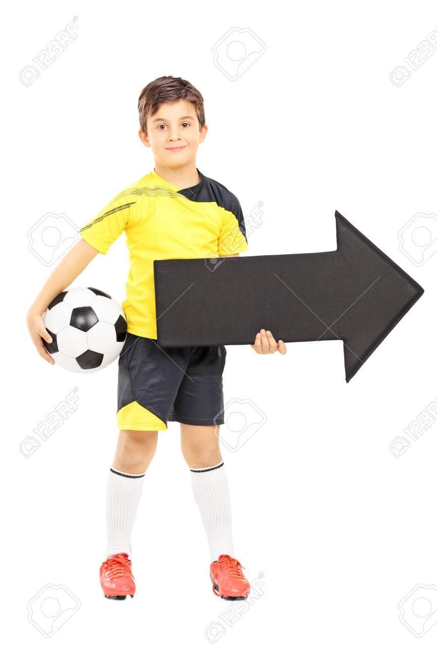 Foto de archivo - Retrato de cuerpo entero de un niño sonriendo en ropa  deportiva sosteniendo una pelota de fútbol y una flecha apuntando hacia la  derecha ... 79bf2f2e4ce4b