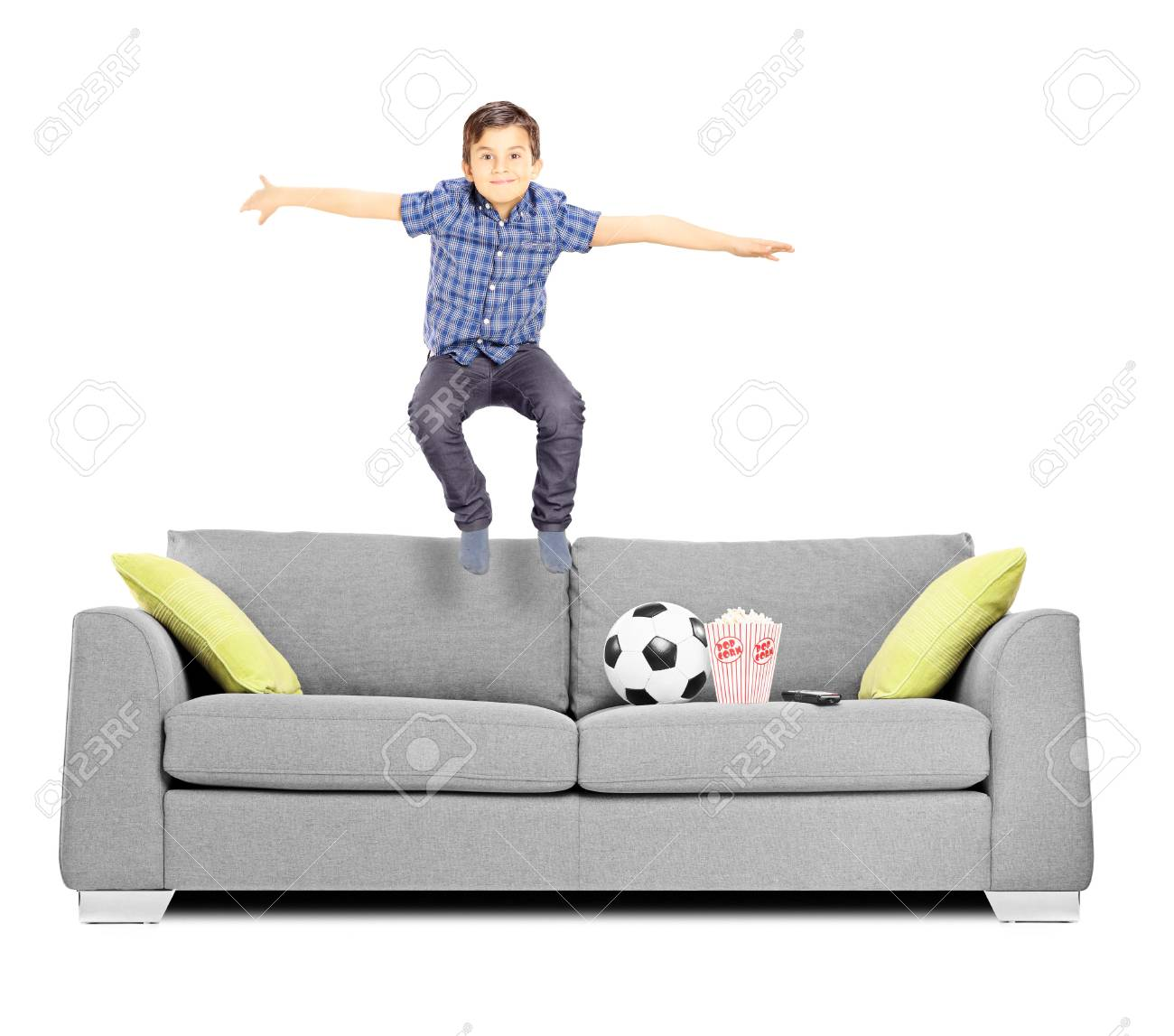 Happy little boy jumping on a sofa isolated on white background Stock Photo - 24594089