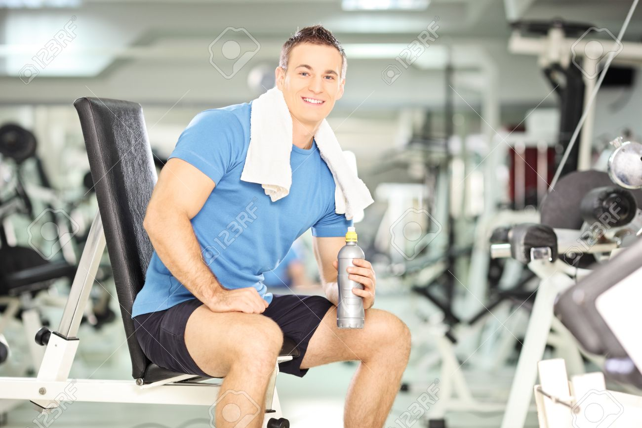 Smiling man seated on a bench drinking water after exercise in smiling man seated on a bench drinking water after exercise in fitness gym with very sciox Choice Image