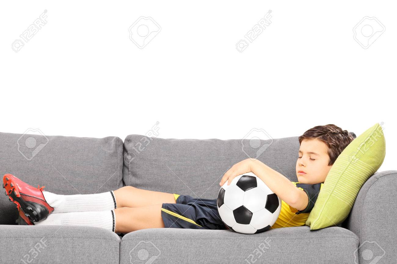 Boy in sportswear with a football sleeping on a modern sofa isolated on white background Stock Photo - 24594188