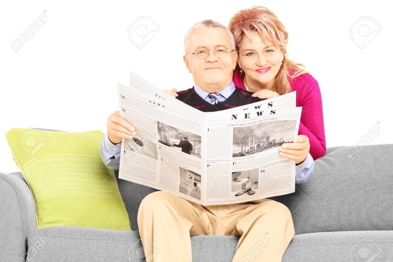 Middle aged couple with newspaper sitting on a couch isolated on white background Stock Photo - 24594211
