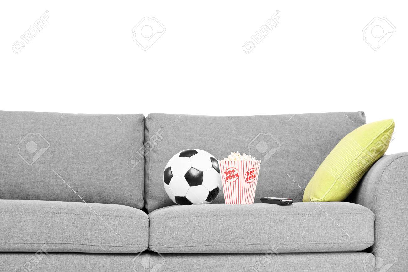 Studio shot of a couch with soccer ball and popcorn box on it isolated on  white